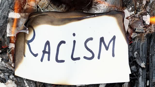 flames burn a piece of paper with the word racism - nazism stock videos & royalty-free footage