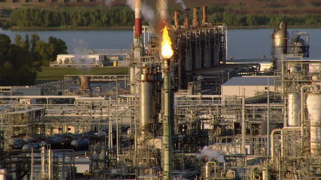 vídeos de stock e filmes b-roll de flames burn at the top of a smokestack in an oil refinery. - refinaria de petróleo