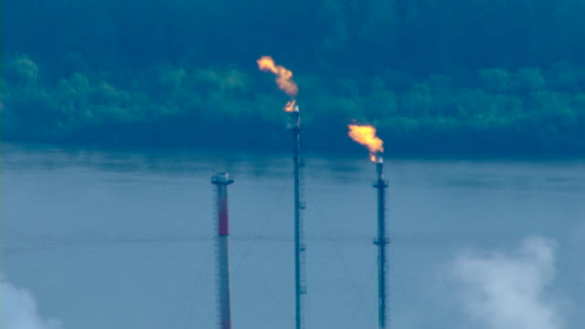 Flames burn from flare stacks at an oil refinery.