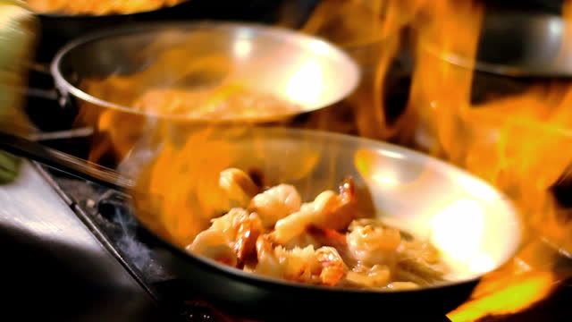 Flames burn under a frying pan filled with shrimp.