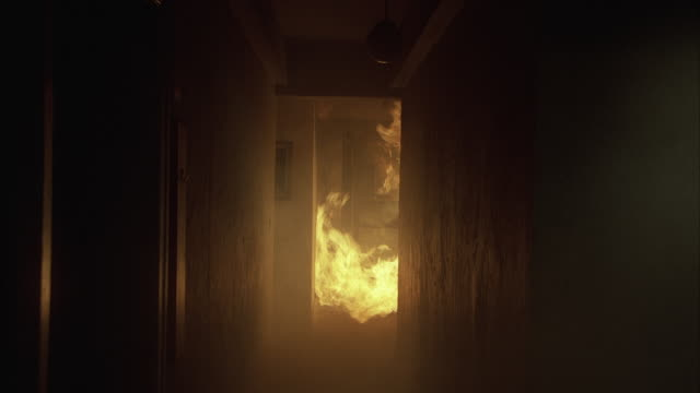 Flames engulf a room at the end of a corridor.