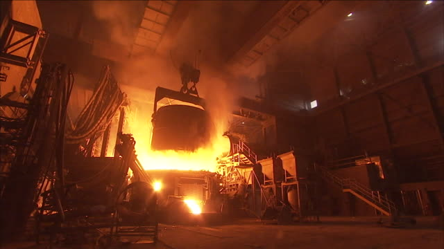 flames erupt from a furnace in a steel factory as a bucket of molten steel moves overhead. - furnace stock videos & royalty-free footage