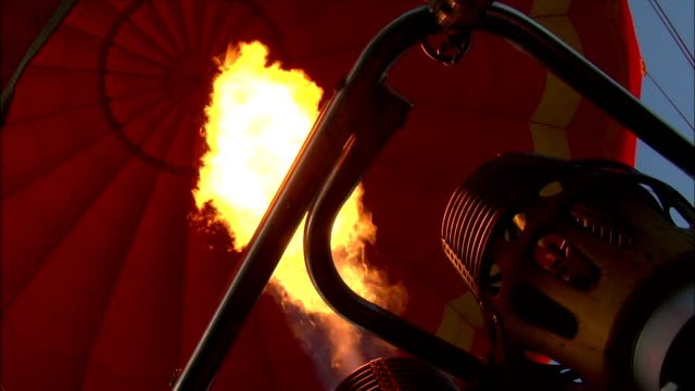 flames erupt from the burner on a hot air balloon. - hot air balloon stock videos & royalty-free footage