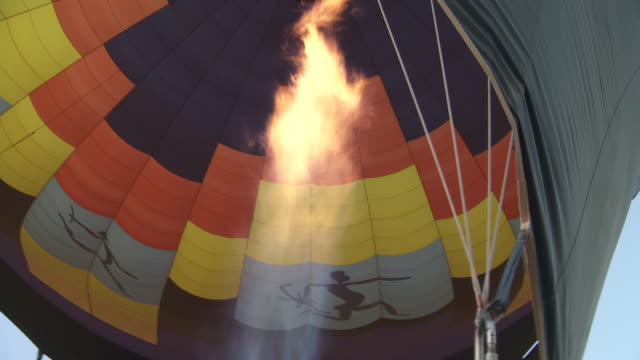 vídeos de stock e filmes b-roll de flames fill a hot air balloon before takeoff. - soprar