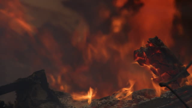 flames flare above the ash-coated charred rubble of a house fire - flammenmeer stock-videos und b-roll-filmmaterial