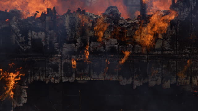 Flames flicker on charred siding in the rubble of a house fire