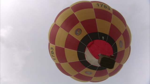 flames flow into a hot air balloon as it rises overhead. available in hd. - balloons stock videos and b-roll footage
