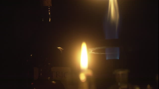 flames from a bunsen burner continue to flicker after a nearby candle goes out. - bunsen burner stock videos & royalty-free footage