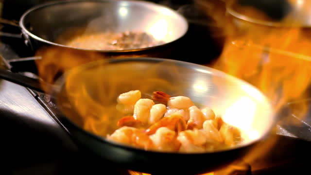 Flames heat a skillet full of shrimp on a stove.