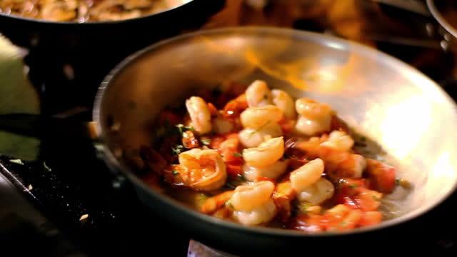 vídeos y material grabado en eventos de stock de las llamas calientan una sartén llena de camarones en una estufa. - llama fuego