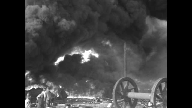 flames high in air and dark smoke, oil derricks nearby and in bg as workers help to contain blaze, some shoveling, looks like water covering some... - fire hose stock videos & royalty-free footage