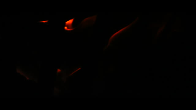 Flames in brazier, black background, close up