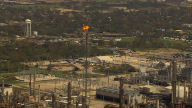 flames leap from a flare stack at a sprawling oil refinery in an aerial view. - 燃焼煙突点の映像素材/bロール