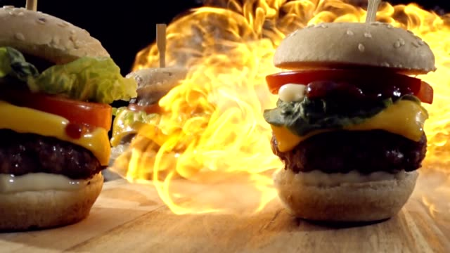 flames over mini cheese burgers in slow motion - hamburger stock videos & royalty-free footage