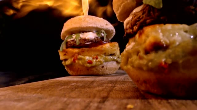 Flames over Veggie Burger with Grilled Cheese, Mushroom, Guacamole and Arugula in Slow Motion