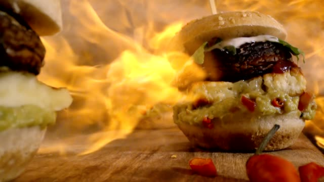 flames over veggie burger with grilled cheese, mushroom, guacamole and arugula in slow motion - portobello mushroom stock videos & royalty-free footage