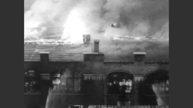 flames raging from the roof of a brussels department store / fire crews with hoses try to put out the fire / people walking down the street looking... - 1967 bildbanksvideor och videomaterial från bakom kulisserna