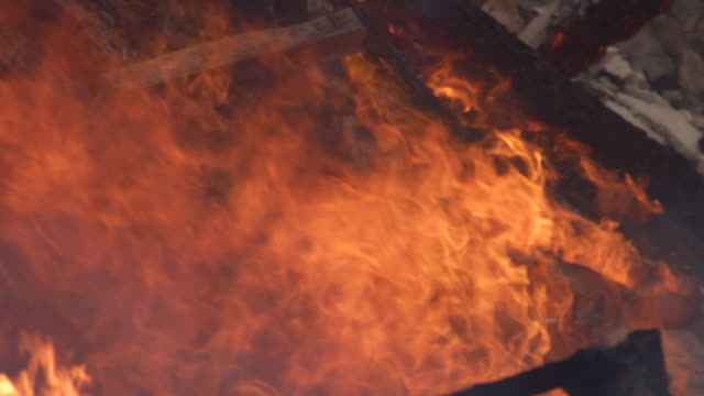 Flames rise above a pile of timbers reduced to rubble in a house fire