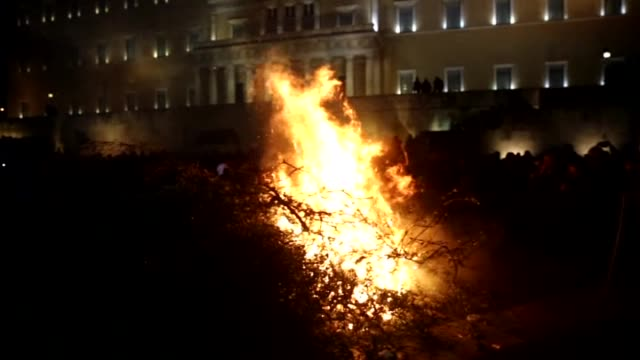 flames rise as greek farmers stage a rally against pension reform in front of the greek parliament at the syntagma square in athens on february 12... - griechische flagge stock-videos und b-roll-filmmaterial