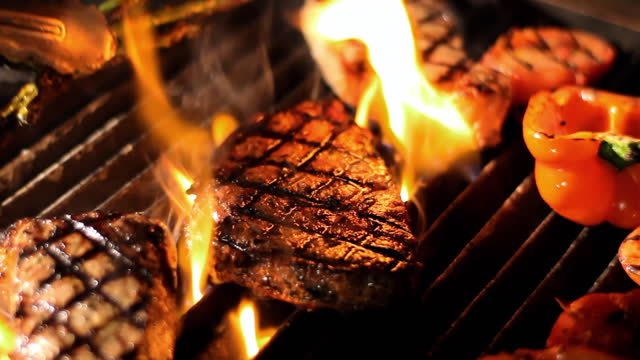 Flames rise from a grill with steak and vegetables cooking.