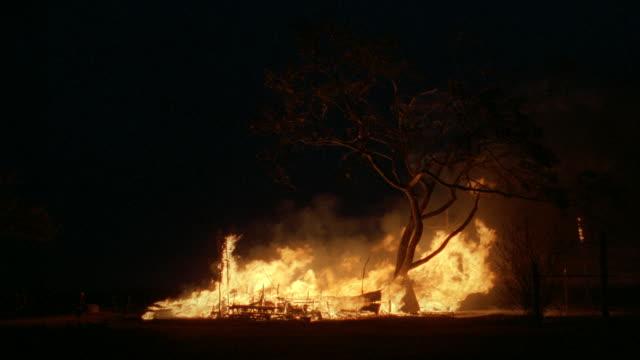 vidéos et rushes de flames rise from the rubble of a farmhouse fire. - brûler