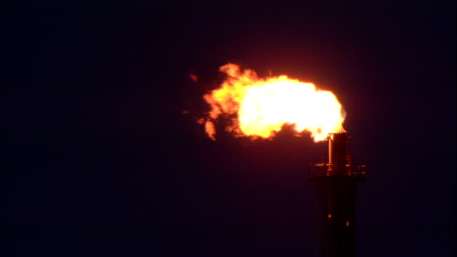 flames shoot out of an oil refinery stack. - flame stock videos & royalty-free footage