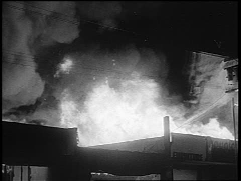 B/W 1965 flames smoke of building on fire at night in Watts race riots / Los Angeles / newsreel