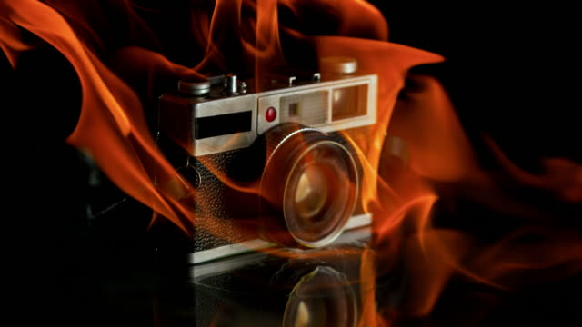 SLO MO Flames wrapping up a camera on a black background