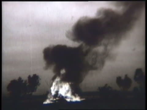 vídeos de stock, filmes e b-roll de a flaming airplane crashes in a field; a biplane flies low over a war zone. - guerra