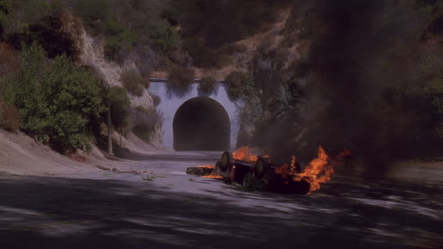 A flaming car flips over onto its roof outside a tunnel, sending up dense black smoke.