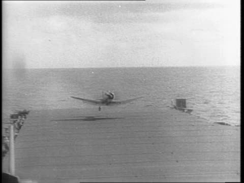 vídeos de stock, filmes e b-roll de flaming japanese bomber plane crashes into the ocean / a damaged american hellcat plane comes in for a landing on an aircraft carrier rescue crew... - guerra do pacífico