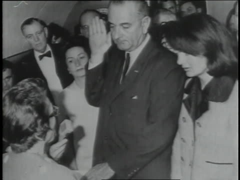 flanked by lady bird johnson and jacqueline kennedy, lyndon johnson takes the oath of office on air force one. - jacqueline kennedy stock videos and b-roll footage
