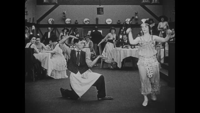 stockvideo's en b-roll-footage met 1918 flapper girl dances awkwardly in crowded restaurant as cool headed waiter (buster keaton) joins her for a dance session - 1920
