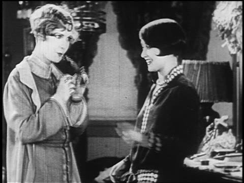 b/w 1925 flapper giving perfume bottle to second flapper who sprays it on herself - parfum stock-videos und b-roll-filmmaterial