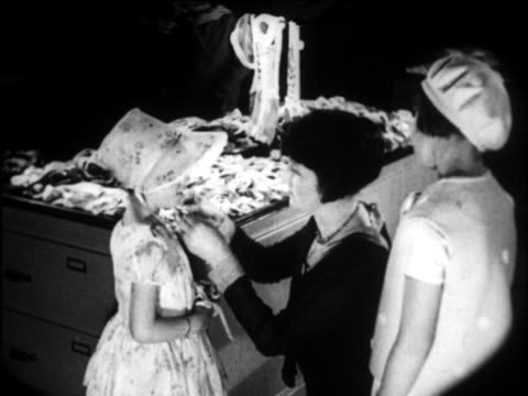 b/w 1924 flapper woman tying bonnet on little girl in clothing store / newsreel - familie mit zwei kindern stock-videos und b-roll-filmmaterial