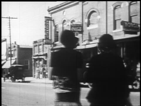 b/w 1925 rear view 2 flappers crossing street in town / newsreel - 1925 stock videos & royalty-free footage