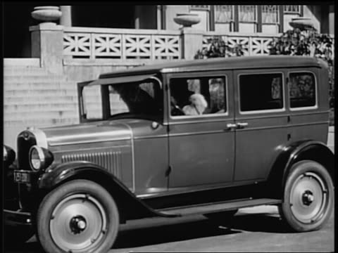 b/w 1928 2 flappers getting out of chevrolet in front of house / industrial - general motors stock videos & royalty-free footage