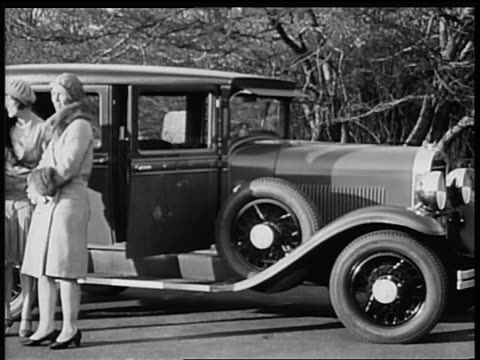 b/w 1928 2 flappers standing in front of oldsmobile car / industrial - 1928 stock videos & royalty-free footage