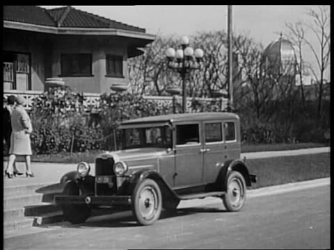B/W 1928 2 flappers walking away from Chevrolet in front of house / industrial