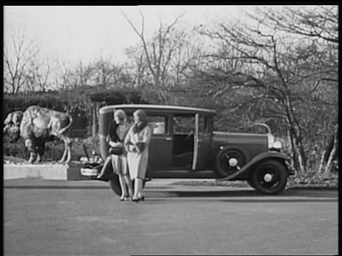 vidéos et rushes de b/w 1928 2 flappers walking away from oldsmobile car / industrial - 1928
