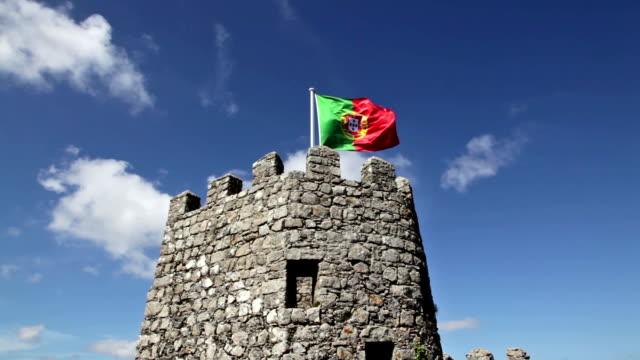 vídeos de stock, filmes e b-roll de abanar bandeira de portugal contra nublado céu azul - castelo