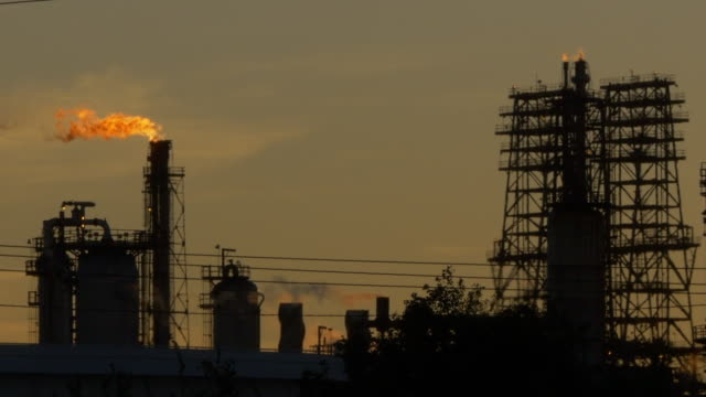 vidéos et rushes de flare stack and oil refinery plant at sunset - gaz