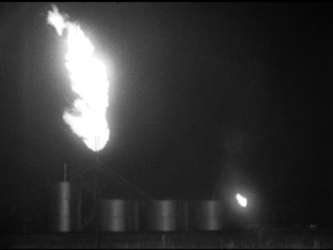 flare stack flame burning, fire, burning off excess gas or oil at refinery w/ tanks below, smaller flame on side, wind blowing smoke into lens,... - 燃焼煙突点の映像素材/bロール