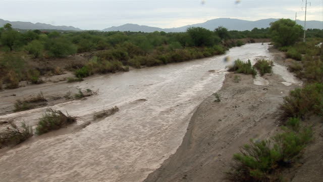 a flash flood fills a dry riverbed in tucson, arizona. - riverbed stock videos & royalty-free footage
