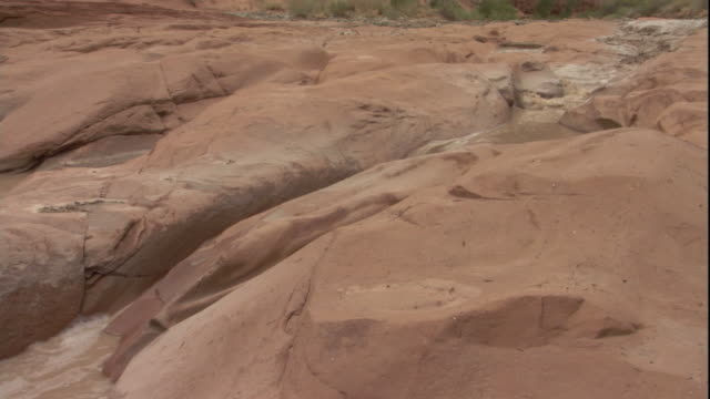A flash flood races over sandstone channels. Available in HD.