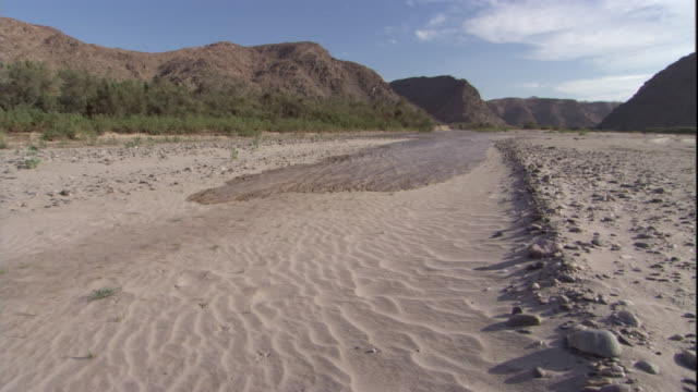 flash flood water pours over dry river bed, skeleton coast, namibia. available in hd. - dürre stock-videos und b-roll-filmmaterial