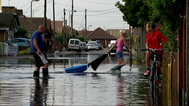 vídeos de stock, filmes e b-roll de flash floods in essex car driving through floodwater woman wearing wellington boots wading through floodwater people in flooded street bob kitts and... - vadear