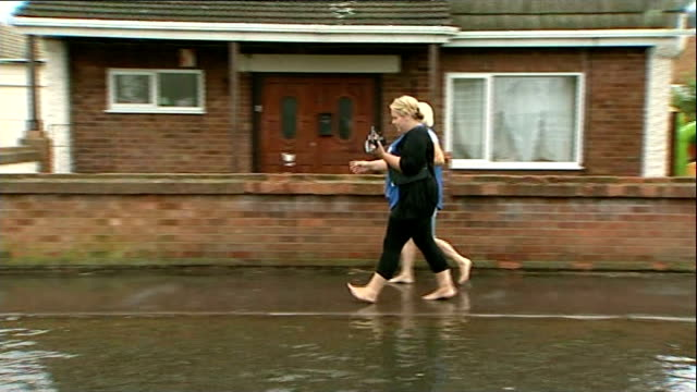 Flash floods in Essex EXT Royal Mail van driving along flooded road Two women along street Canvey Island West interview SOT Woman dragging bags of...