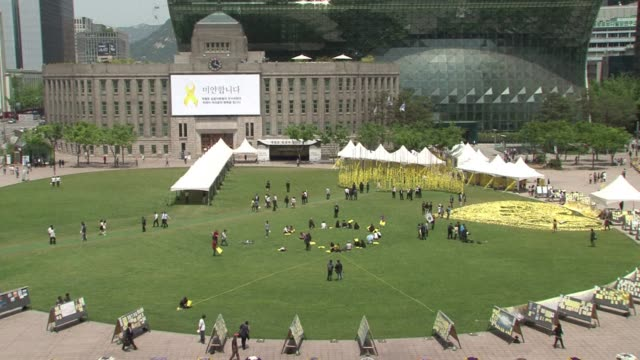 a flash mob gathers in seoul in the shape of a yellow ribbon in memory of the victims of south koreas ferry disaster one month ago - flash mob stock videos and b-roll footage