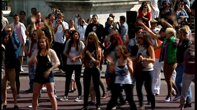 flash mob outside buckingham palace / rehearsals for royal reception england london buckingham palace ext **song 'we will rock you' by queen heard... - flash mob stock videos and b-roll footage